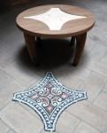 struttura in legno di un tavolino con vicino il mosaico realizzato da montare al suo interno